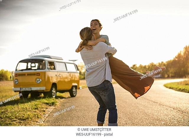 Happy couple doing a road trip with a camper, embracing on the road