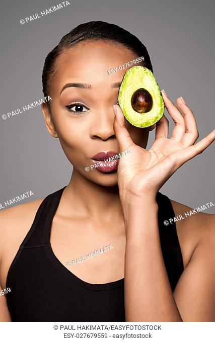 Beautiful healthy happy black asian woman holding delicious avocado super fruit in front of eye