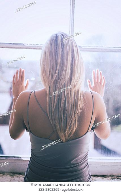 Rear view of a blond woman standing by the window