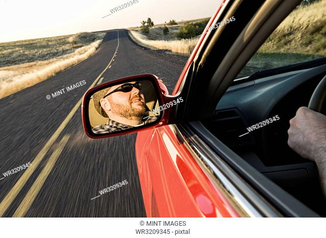 View in the rear view drivers mirror of a Caucasian male driving a car on a road trip in eastern Washington State, USA