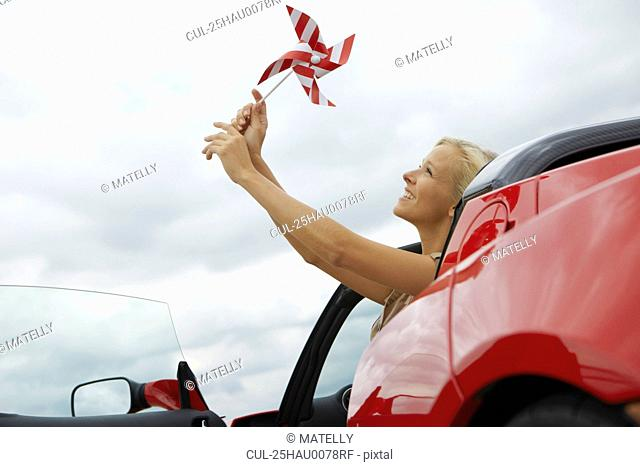 Girl holding windmill in an electric car