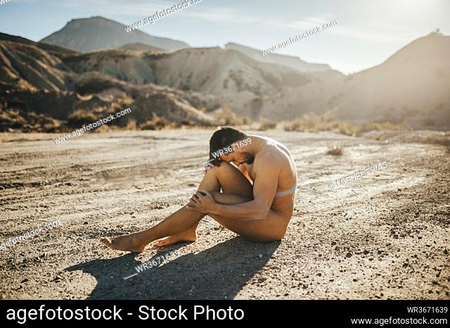 Naked mid adult man sitting at desert against mountains during sunny day