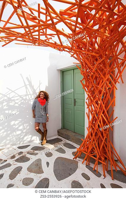 Woman posing with an orange scarf near a whitewashed house in town center, Mykonos, Cyclades Islands, Greek Islands, Greece, Europe