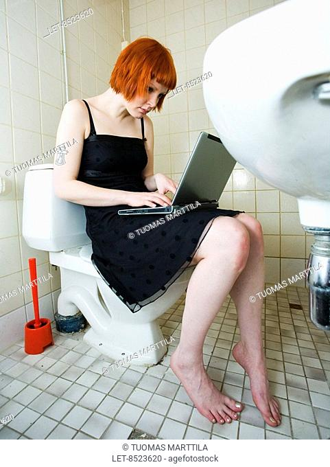 A woman is sitting in a bathroom and typing with the computer