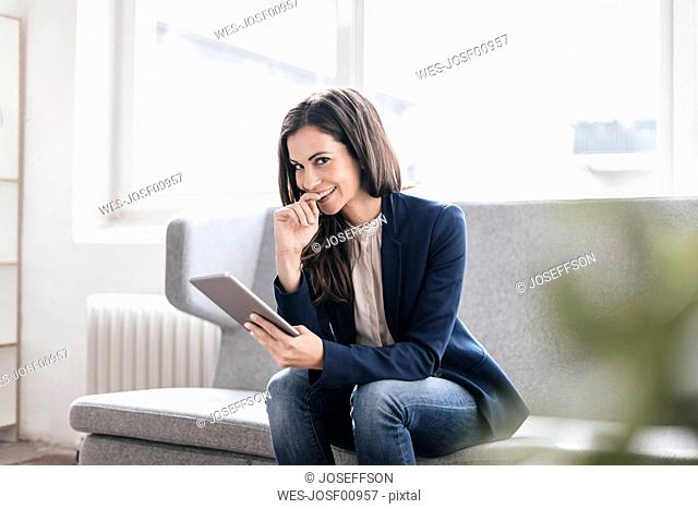 Portrait of smiling businesswoman with tablet on couch
