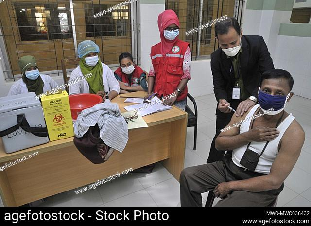 Health workers vaccinating people during the first-stage of the coronavirus vaccination program at Osmani Medical College and Hospital