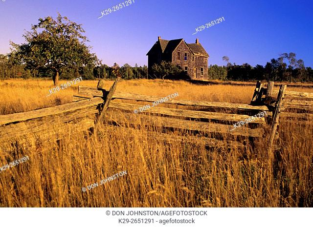 Cedar split-rail fence with abandoned house and autumn grasses, near Gore Bay, Ontario, Canada
