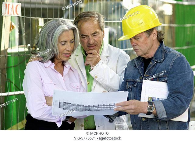 Germany, HAMBURG, 30.06.2008, Ein aelteres Paar besichtigt eine Baustelle und lasst sich vom Architekten den Grundriss erklaeren