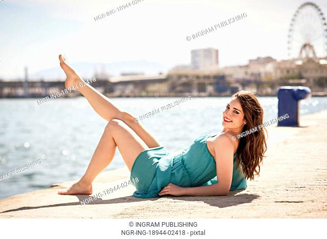 Beautiful young woman with blue eyes wearing blue dress in the beach. Happy girl with beautiful legs