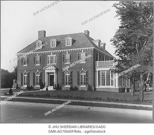 Landscape shot of a three-story brick house with a white entrance, white annexed sun room with a balcony on top, a chimney