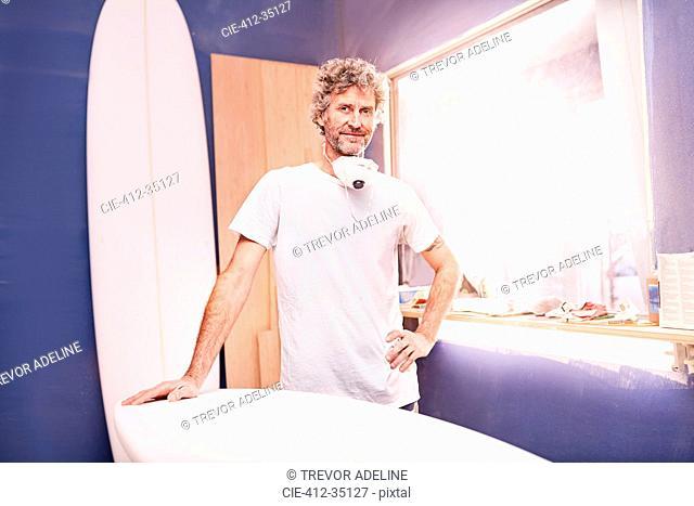 Portrait confident male surfboard designer sanding surfboard in workshop