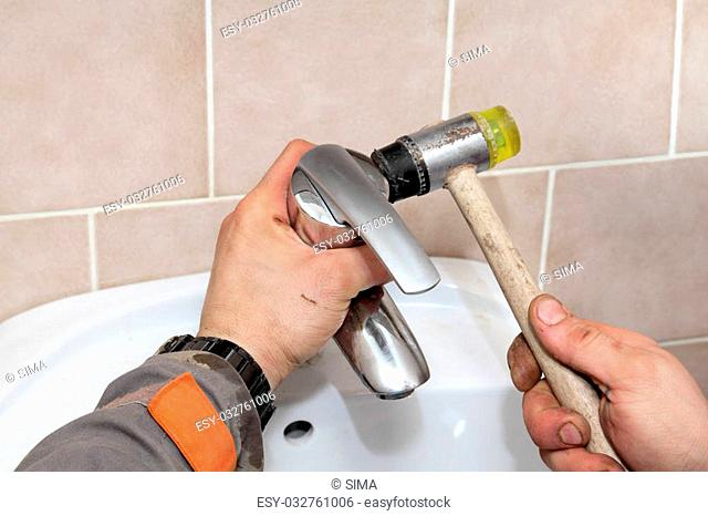 Plumber fixing water tap in a bathroom using hammer
