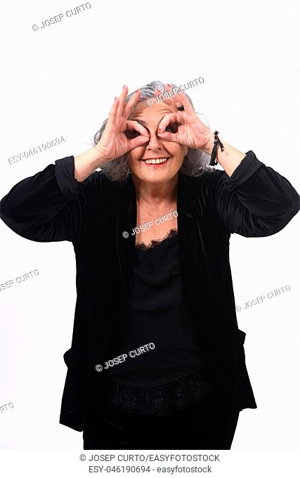 senior woman looking through fingers as if wearing glasses on white background