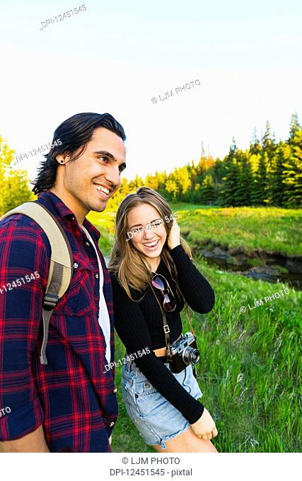 Young couple walking together in a city park in autumn taking a camera with them on the adventure; Edmonton, Alberta, Canada