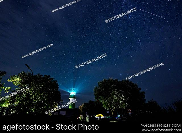 dpatop - 13 August 2021, Schleswig-Holstein, Strande: A shooting star passes over the Bülk lighthouse on the shore of the Baltic Sea