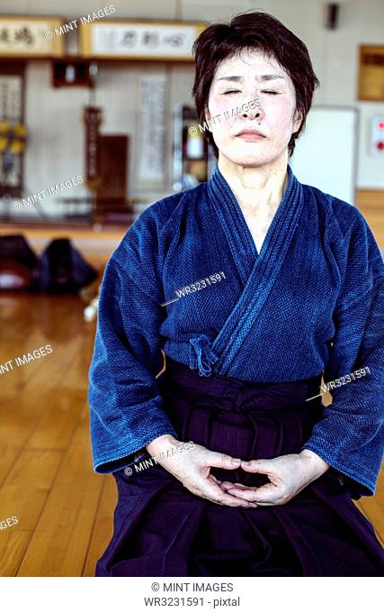 Female Japanese Kendo fighter kneeling on wooden floor, meditating
