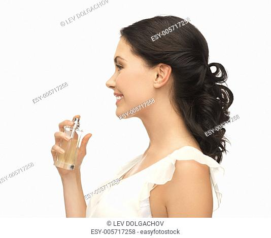 picture of beautiful woman spraying perfume on her neck