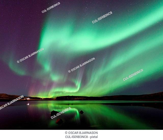 Aurora borealis over water at night, Thingvellir, Iceland