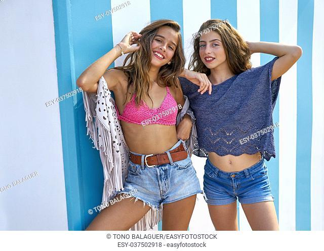 Best friends teen girls happy portrait in a summer blue stripes background