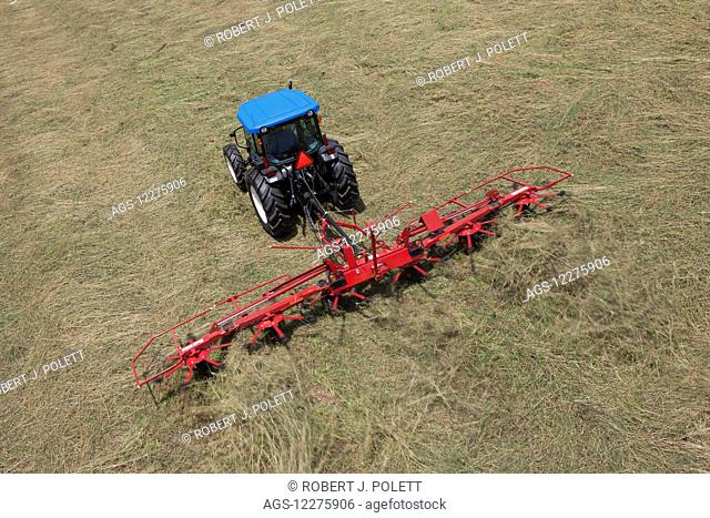 High angle view of New Holland T4050 tractor with H5270 tedder in alfalfa; New Holland, Pennsylvania, United States of America