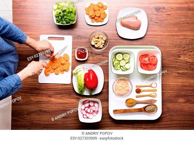 High Angle View Of Woman Cutting Vegetable On Chopping Board While Cooking In Kitchen