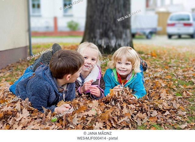 Three children lying at autumn foliage