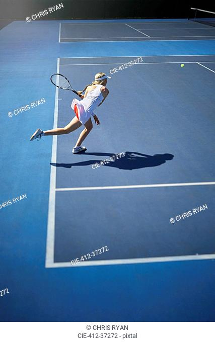 Young female tennis player playing tennis, swinging tennis racket on sunny blue tennis court