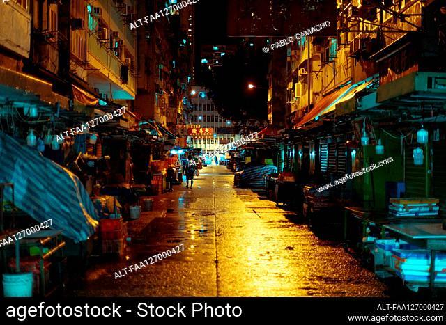 View of street and half-closed market stall at night in Hong Kong