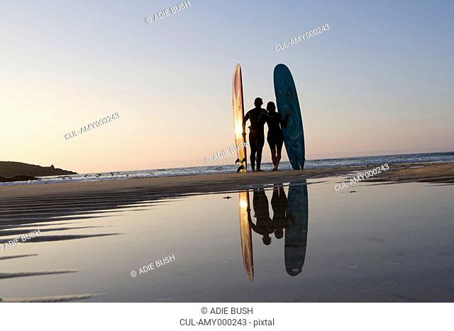 Couple standing on beach with surfboards