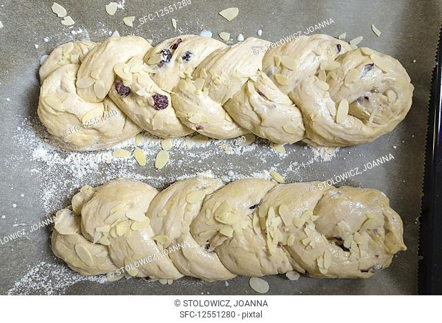 Unbaked yeast buns with raisins and almond flakes