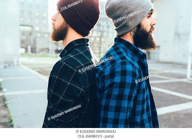 Portrait of two young male hipsters in knit hats back to back in city