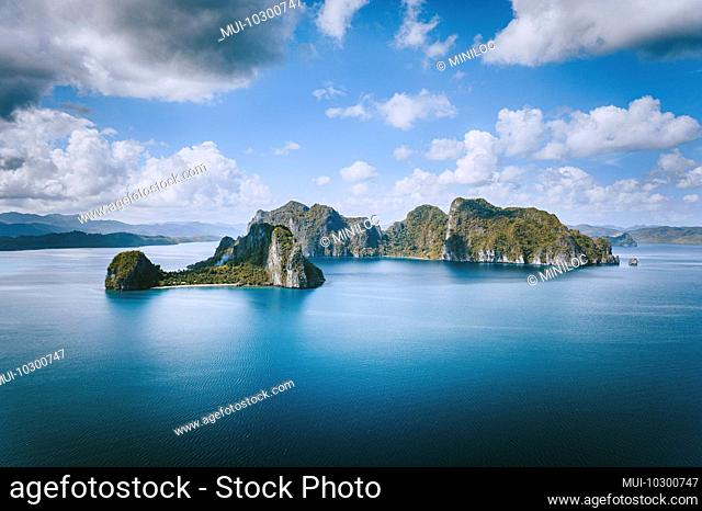 El Nido, Palawan, Philippines. Panoramic aerial view lonely tourist boat in open sea with exotic tropical Pinagbuyutan island standing out in ocean