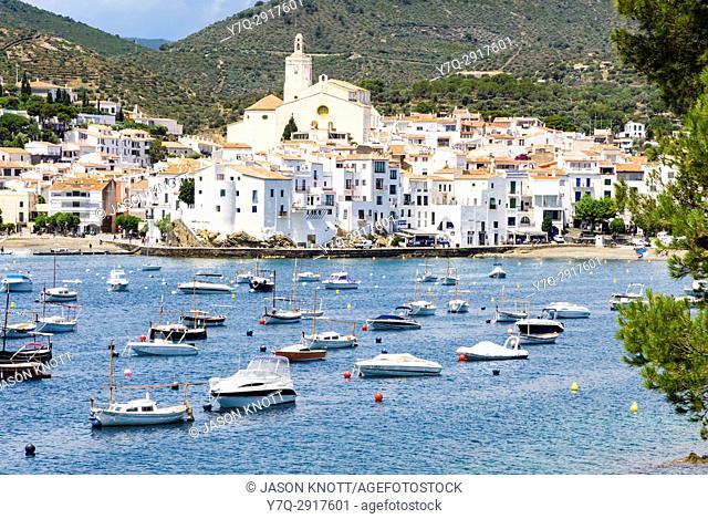 Whitewashed village of Cadaqués topped by the Church of Santa Maria overlooking boats in the blue waters of Cadaqués Bay, Cadaqués, Catalonia, Spain