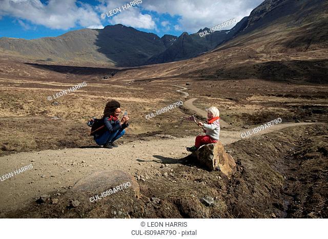 Mother taking photo of son, Fairy Pools, Isle of Skye, Hebrides, Scotland