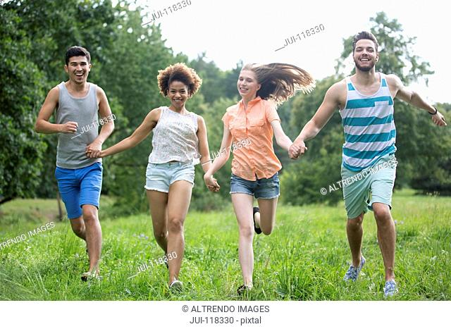 Portrait Of Young Couples Running Through Summer Field