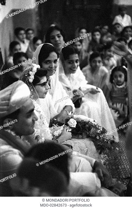 Bride and groom attending the wedding ceremony with guests. Zanzibar, 1950s