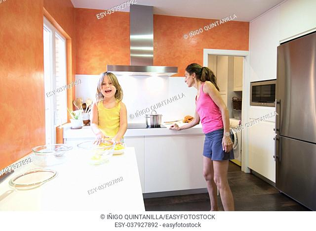 Four years old blonde child preparing raw potatoes to cook in the kitchen, looking and smiling, next to woman mother