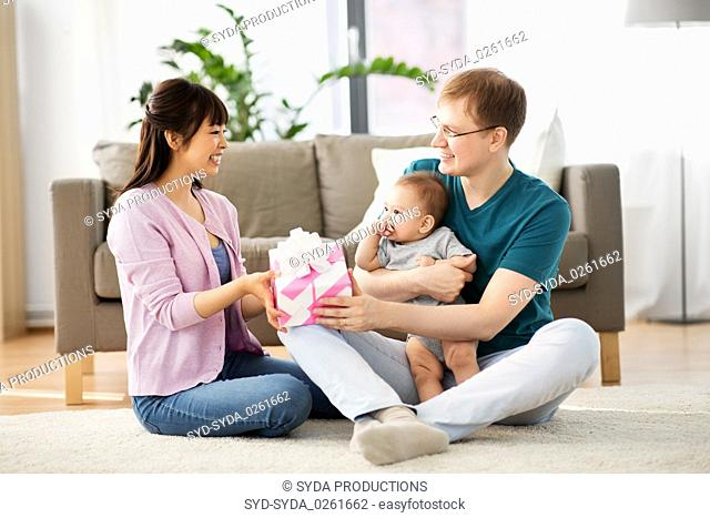 happy family with gift and baby boy at home