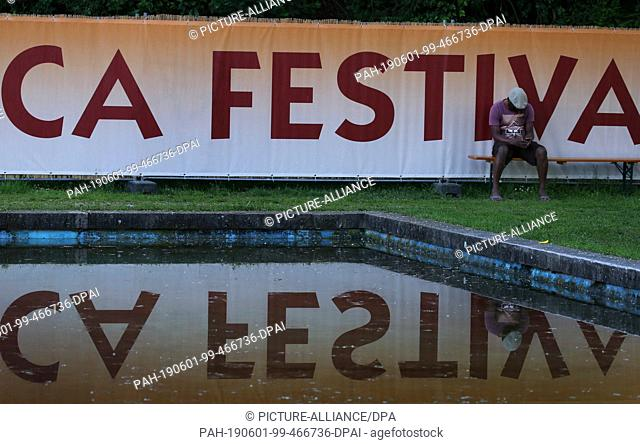 31 May 2019, Bavaria, Würzburg: The logo of the Africa Festival is reflected in a water basin. The Africa Festival is one of the largest festivals for African...