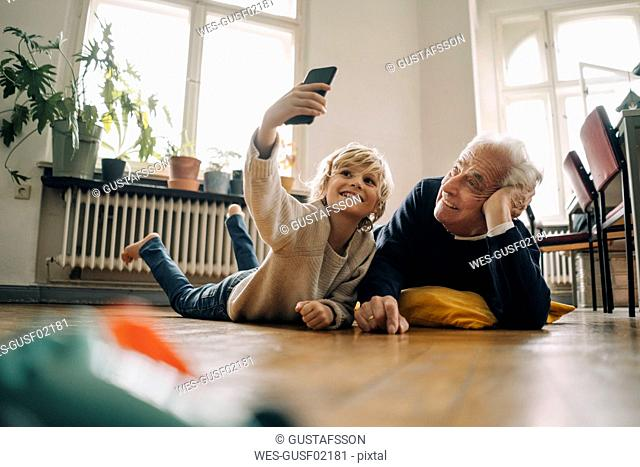 Grandfather and grandson lying on the floor at home taking a selfie