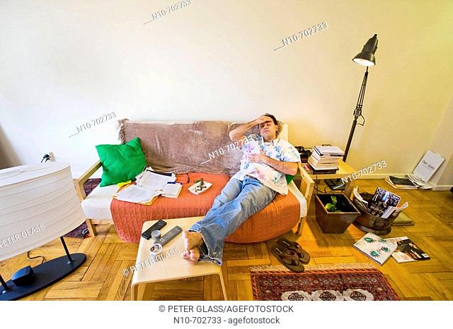 Young man sitting on the sofa in his apartment