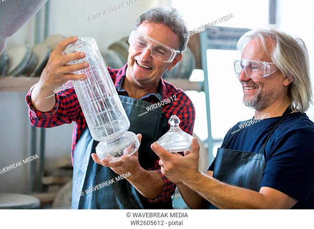 Glassblower and a colleague looking glassware