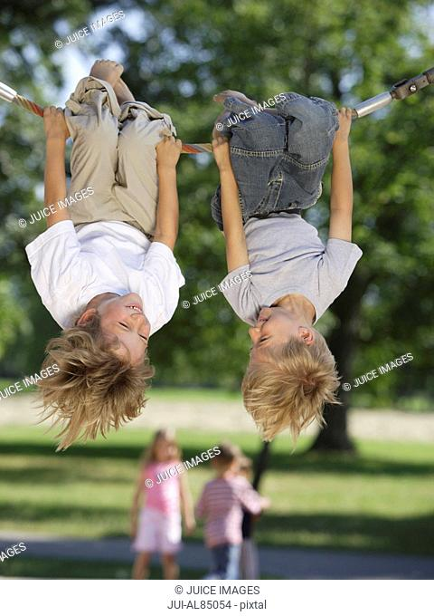 Two boys hanging upside down on rope at playground