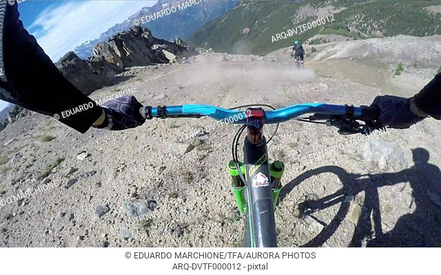 POV past hands of mountain biker in descent from mountain ridge
