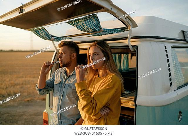 Couple brushing teeth at camper van in rural landscape at sunset
