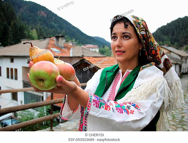 A beautiful young woman in traditional Bulgarian folklore costume is holding fresh fruit