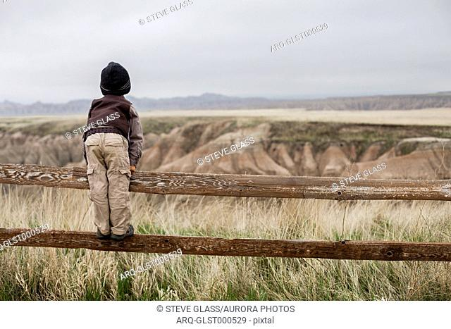 A 4 year old Japanese American boy dressed as an explorer with a hat and vest shoots surveys the land while standing on the rail of a wooden fence in as he...