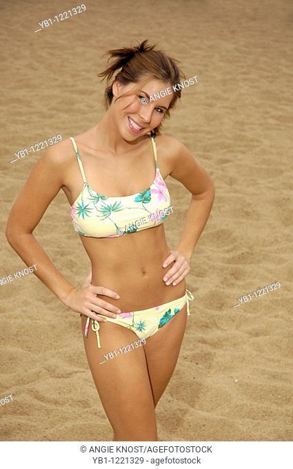 Attractive woman on sandy beach, wearing floral bikini