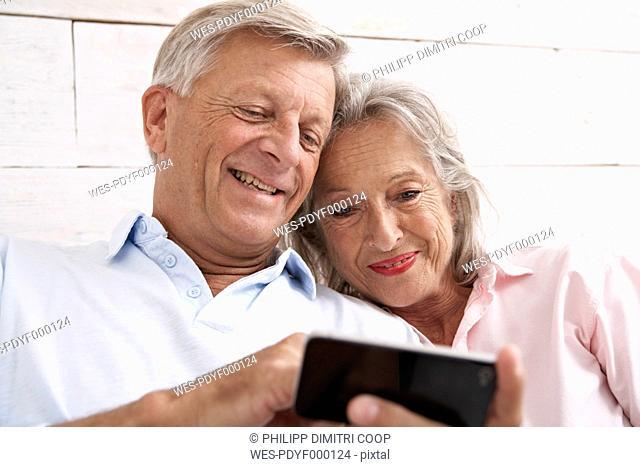 Spain, Senior couple using mobile phone, smiling
