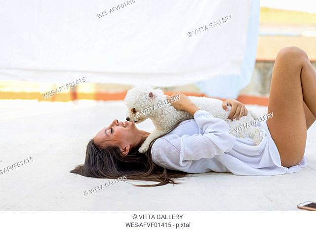 Happy young woman cuddling with dog on roof terrace